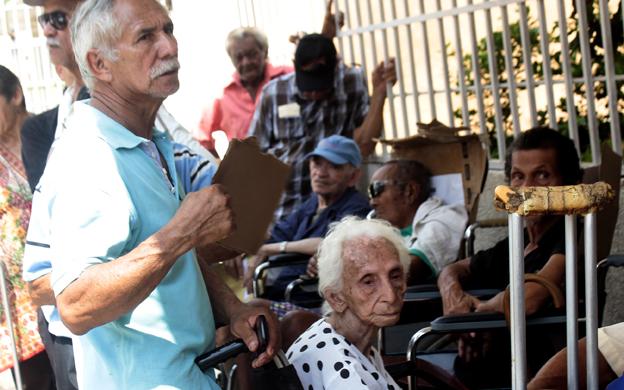 Bajo el inclemente sol de Maracaibo, con hambre y sed los pensionados hicieron ayer largas colas para poder cobrar el beneficio. (Foto: José Gil)