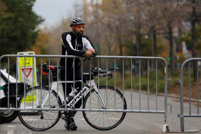 Misha Thomas, who said he rode from Harlem to pay his respects for victims of Tuesday's attack, stands outside a police barricade on the bike path next to West Street a day after a man driving a rented pickup truck mowed down pedestrians and cyclists on a bike path alongside the Hudson River in New York City, in New York, U.S. November 1, 2017. REUTERS/Shannon Stapleton