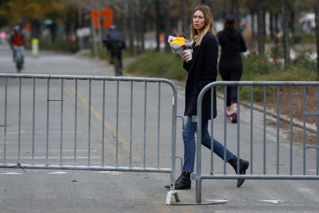 A woman, who a NYC Park ranger said asked where she could lay flowers for victims of Tuesday's attack, walks by a police barricade on the bike path next to West Street a day after a man driving a rented pickup truck mowed down pedestrians and cyclists on a bike path alongside the Hudson River in New York City, U.S. November 1, 2017. REUTERS/Shannon Stapleton
