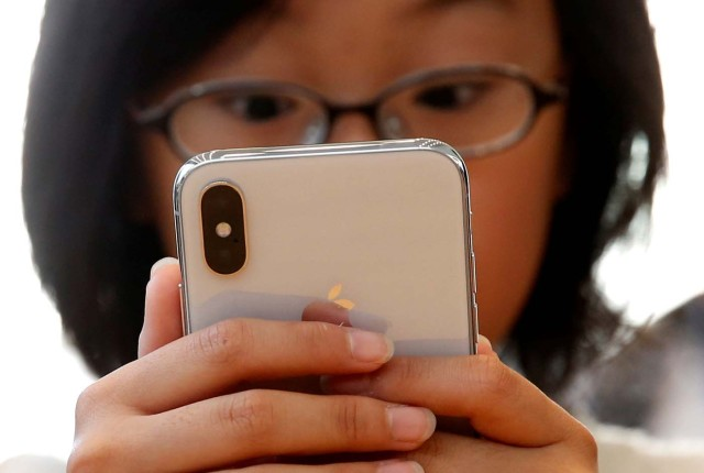 A customer looks at Apple's new iPhone X after it goes on sale at the Apple Store in Tokyo's Omotesando shopping district, Japan, November 3, 2017.REUTERS/Toru Hanai