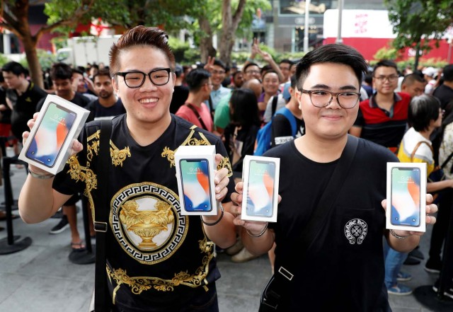 REFILE - ADDING CUSTOMER'S NAME: First customers to buy iPhone X Kittiwat Wang, 22, and Supakorn Rieksiri, also known as Mod, , 22, of Bangkok pose with their iPhone X at the Apple store in Singapore November 3, 2017. REUTERS/Edgar Su