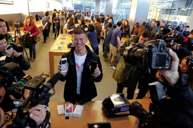 The first customer shows his new iPhone X after buying it at an Apple Store in Beijing, China November 3, 2017. REUTERS/Damir Sagolj