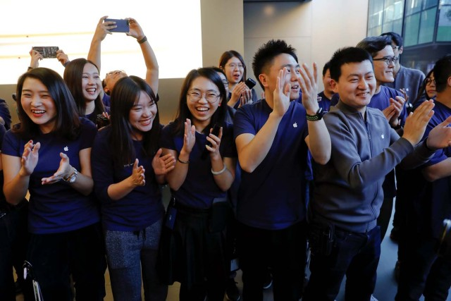 Apple staff cheer as the first customer for iPhone X enters an Apple Store in Beijing, China November 3, 2017. REUTERS/Damir Sagolj