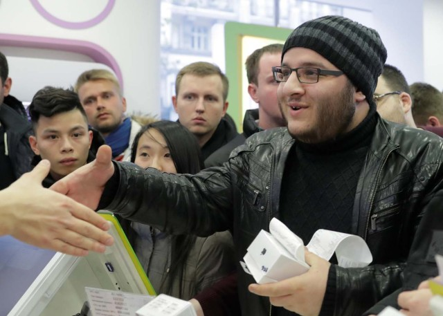 A customer who has just bought Apple's new iPhone X shakes hands with a store employee during its global launch at a cell phone store in central Moscow, Russia November 3, 2017. REUTERS/Tatyana Makeyeva