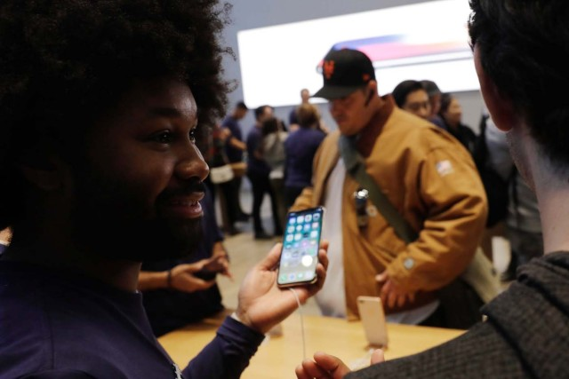 An Apple sales associate speaks with a customer waiting to purchase a new iPhone X in New York, U.S., November 3, 2017. REUTERS/Lucas Jackson