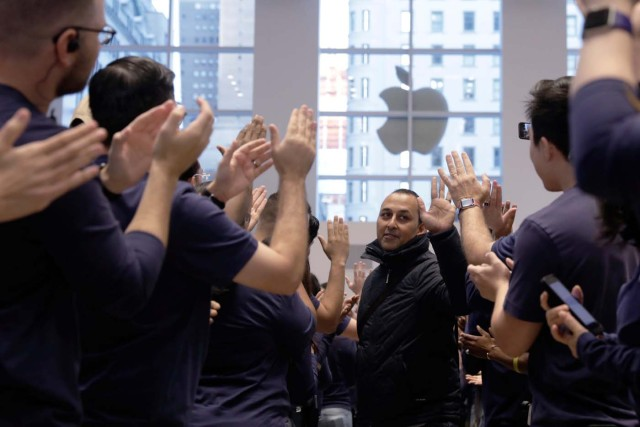 A customer is greeted by Apple employees as he enters an Apple store to purchase an iPhone X in New York, U.S., November 3, 2017. REUTERS/Lucas Jackson