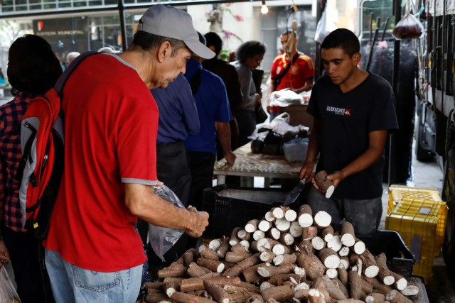 A man buys yucca at a street market in Caracas, Venezuela November 3, 2017. Picture taken November 3, 2017. REUTERS/Marco Bello