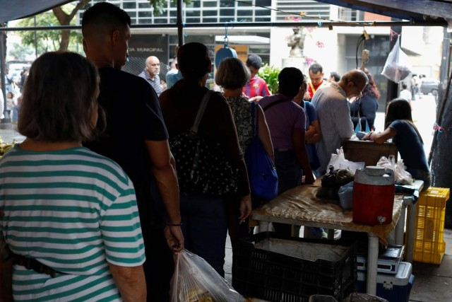 People line up to pay for their fruits and vegetables at a street market in Caracas, Venezuela November 3, 2017. Picture taken November 3, 2017. REUTERS/Marco Bello