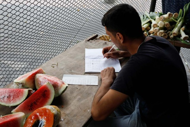 A vendor takes sales notes at a street market in Caracas, Venezuela November 3, 2017. Picture taken November 3, 2017. REUTERS/Marco Bello