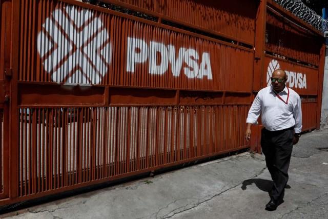 Imagen de archivo. Un hombre pasa frente a una puerta con el logo de la petrolera estatal PDVSA en Caracas, Venezuela el 3 de noviembre de 2017. REUTERS / Marco Bello