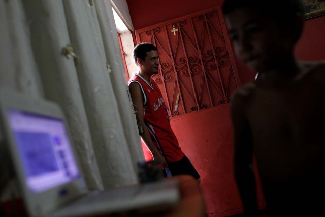 """Willian Torres (L), stands in the doorway to his house on the outskirts of Caracas, Venezuela, October 14, 2017. Torres wagered money on """"Los Animalitos"""" (or the Little Animals) betting game during the week, planning to go to the beach with his family with the prize money, but he didn't win. REUTERS/Ricardo Moraes SEARCH """"MORAES GAMBLING"""" FOR THIS STORY. SEARCH """"WIDER IMAGE"""" FOR ALL STORIES."""