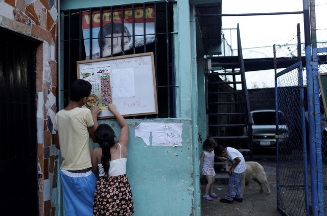 """Children check the list for """"Los Animalitos"""" (or the Little Animals) betting game on the outskirts of Caracas, Venezuela, October 6, 2017. REUTERS/Ricardo Moraes SEARCH """"MORAES GAMBLING"""" FOR THIS STORY. SEARCH """"WIDER IMAGE"""" FOR ALL STORIES."""