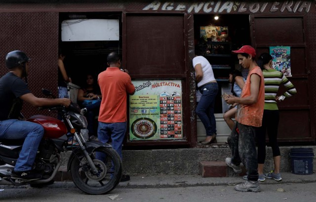 """People wager money on """"Los Animalitos"""" (or the Little Animals) betting game on the outskirts of Caracas, Venezuela, October 9, 2017. REUTERS/Ricardo Moraes SEARCH """"MORAES GAMBLING"""" FOR THIS STORY. SEARCH """"WIDER IMAGE"""" FOR ALL STORIES."""
