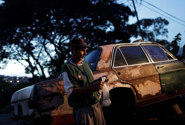 """Eduardo Liendo, 63, who lives inside an old car, holds his prize money which he won on """"Los Animalitos"""" (or the Little Animals) betting game on the outskirts of Caracas, Venezuela, October 11, 2017. REUTERS/Ricardo Moraes SEARCH """"MORAES GAMBLING"""" FOR THIS STORY. SEARCH """"WIDER IMAGE"""" FOR ALL STORIES."""
