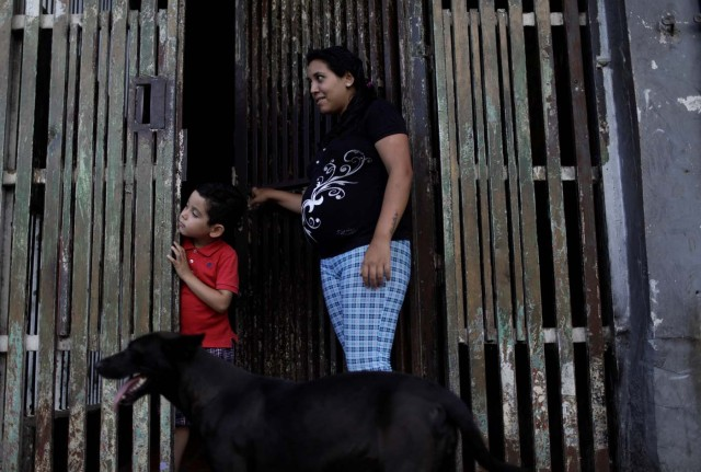 """Natalie Torres, 24, stands with her child, Abel, at the entrance to their building after betting money on """"Los Animalitos"""" (or the Little Animals) betting game on the outskirts of Caracas, Venezuela, October 11, 2017. The last time Torres won a prize on the """"Los Animalitos"""" she bought school supplies for Abel. REUTERS/Ricardo Moraes SEARCH """"MORAES GAMBLING"""" FOR THIS STORY. SEARCH """"WIDER IMAGE"""" FOR ALL STORIES."""