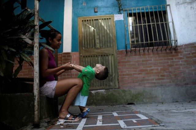 """Veruska Torres plays with her son on the outskirts of Caracas, Venezuela, October 11, 2017. He is wearing a new t-shirt bought with prize money won on """"Los Animalitos"""" (or the Little Animals) betting game. REUTERS/Ricardo Moraes SEARCH """"MORAES GAMBLING"""" FOR THIS STORY. SEARCH """"WIDER IMAGE"""" FOR ALL STORIES."""