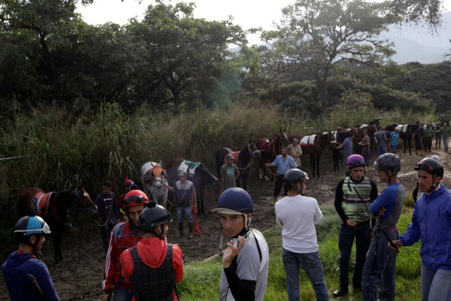 """Jockeys wait with their horses to attend a training session at La Rinconada Hippodrome, in Caracas, Venezuela, October 7, 2017. REUTERS/Ricardo Moraes SEARCH """"MORAES GAMBLING"""" FOR THIS STORY. SEARCH """"WIDER IMAGE"""" FOR ALL STORIES."""