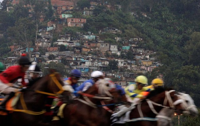 """Competitors take part in a horserace, with a slum or """"barrio"""" in the background at La Rinconada Hippodrome, Caracas, Venezuela, October 8, 2017. REUTERS/Ricardo Moraes SEARCH """"MORAES GAMBLING"""" FOR THIS STORY. SEARCH """"WIDER IMAGE"""" FOR ALL STORIES. TPX IMAGES OF THE DAY."""