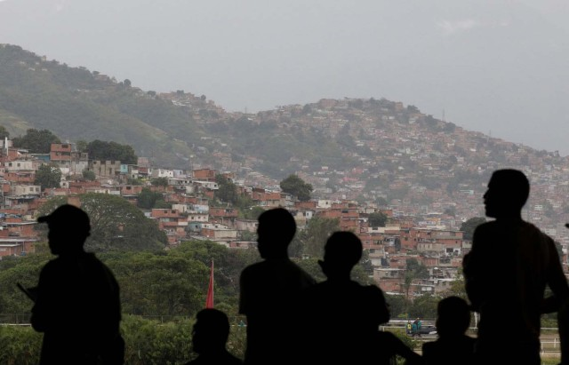"""People watch a horse race, with a slum or """"barrio"""" in the background, at La Rinconada Hippodrome, in Caracas, Venezuela, September 30, 2017. REUTERS/Ricardo Moraes SEARCH """"MORAES GAMBLING"""" FOR THIS STORY. SEARCH """"WIDER IMAGE"""" FOR ALL STORIES."""
