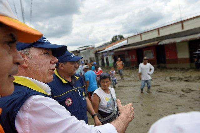 El presidente de Colombia, Juan Manuel Santos, camina por una calle después de las inundaciones y los derrumbes causados por las fuertes lluvias en las que se desbordaba un río, empujó los sedimentos y las rocas hacia las casas y carreteras, en Corinto, el 8 de noviembre de 2017. Presidencia Colombiana.