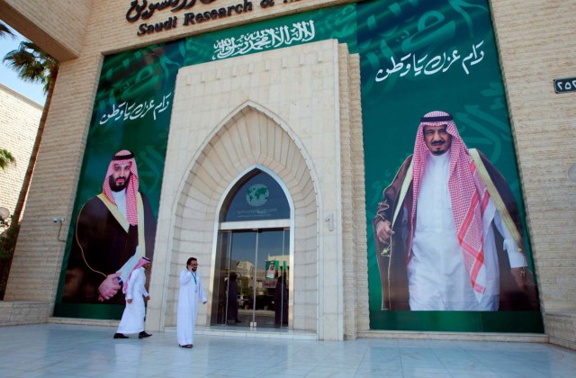 Men walk past posters depicting of Saudi Arabia's King Salman bin Abdulaziz Al Saud and Crown Prince Mohammed bin Salman in Riyadh, Saudi Arabia, November 9, 2017. REUTERS/Faisal Al Nasser NO RESALES. NO ARCHIVE.