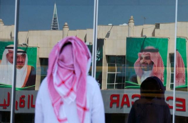 Pictures of Saudi Arabia's King Salman bin Abdulaziz Al Saud and Crown Prince Mohammed bin Salman are reflected in a window as people arrive at a company in Riyadh, Saudi Arabia, November 9, 2017. REUTERS/Faisal Al Nasser NO RESALES. NO ARCHIVES