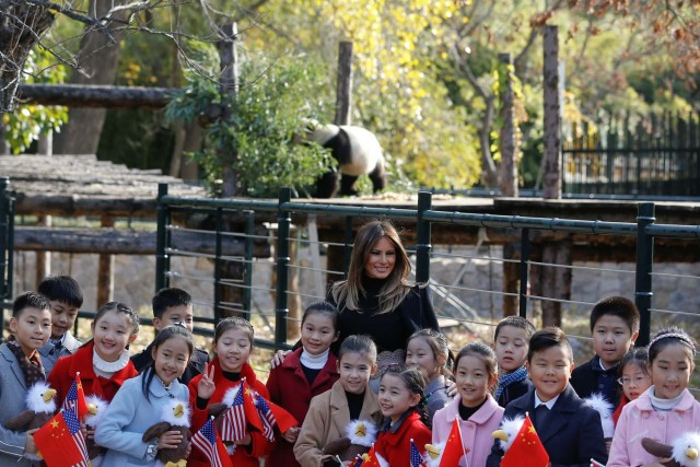 U.S. first lady Melania Trump poses for photos with children in front of a panda section as she visits Beijing Zoo in Beijing, China, November 10, 2017. REUTERS/Thomas Peter