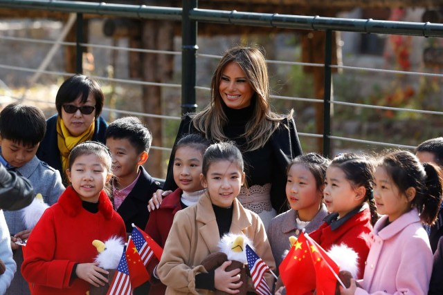U.S. first lady Melania Trump smiles with children holding U.S. and China flags as she visits Beijing Zoo in Beijing, China, November 10, 2017. REUTERS/Thomas Peter