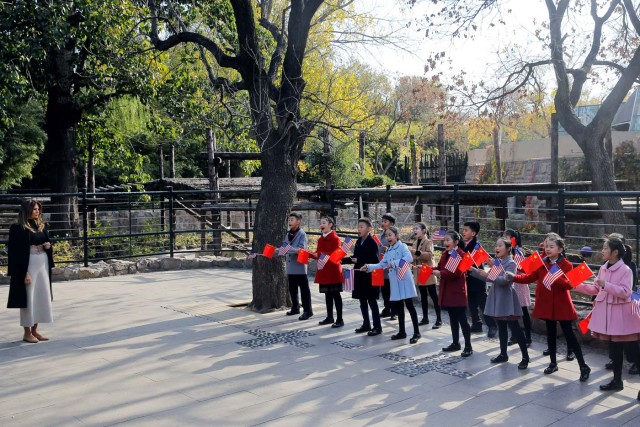 Children holding U.S. and China flags sing for U.S. first lady Melania Trump as she visits Beijing Zoo in Beijing, China, November 10, 2017. REUTERS/Thomas Peter