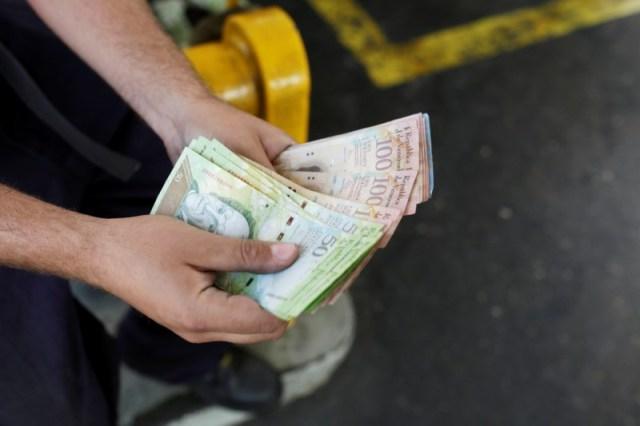 Un trabajador cuenta bolívares venezolanos en una gasolinera de la petrolera estatal venezolana PDVSA en Caracas, Venezuela el 21 de marzo de 2017. REUTERS / Marco Bello