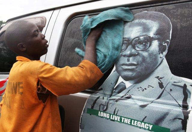 La juventud lava un minibús adornado con la imagen del presidente Robert Mugabe en una terminal de autobuses en Harare, Zimbabwe, el 15 de noviembre de 2017. REUTERS / Philimon Bulawayo NO RESALES. SIN ARCHIVOS