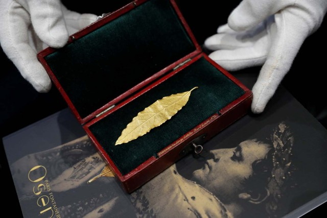 An auctioneer displays a gold laurel leaf from French Emperor Napoleon's imperial crown at the office of the Osenat auction house in Paris, France, November 15, 2017. The leaf will go under the hammer on Sunday and is expected to fetch between 100,000 and 150,000 euros. REUTERS/Philippe Wojazer