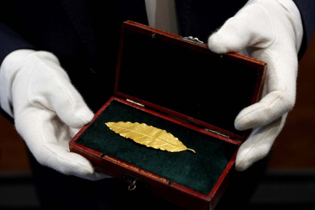 An auctioneer displays a gold laurel leaf from French Emperor Napoleon's imperial crown at the office of the Osenat auction house in Paris, France, November 15, 2017. The leaf will go under the hammer on Sunday and is expected to fetch between 100,000 and 150,000 euros. REUTERS/Philippe Wojazer TPX IMAGES OF THE DAY