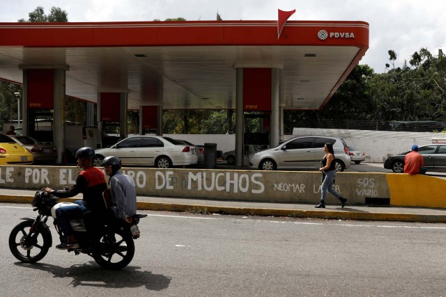 People pass a gas station of Venezuelan state-owned oil company PDVSA in Caracas, Venezuela November 16, 2017. REUTERS/Marco Bello