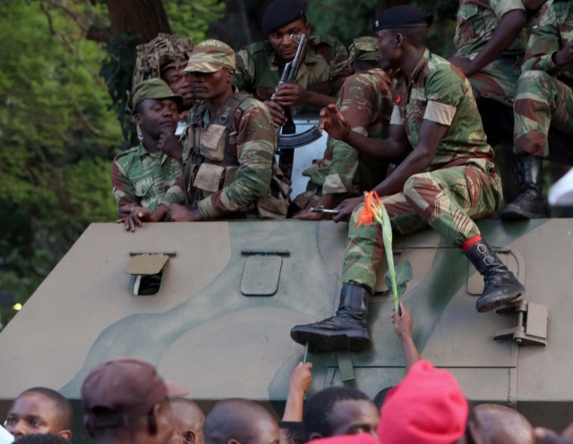 Soldiers sit atop a vehicle as Zimbabweans celebrate after President Robert Mugabe resigns in Harare, Zimbabwe November 21, 2017. REUTERS/Marius Bosch