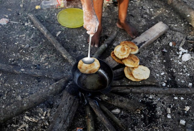 An indigenous Warao woman from the Orinoco Delta in eastern Venezuela, makes bread at a shelter in Pacaraima, Roraima state, Brazil November 15, 2017. Picture taken November 15, 2017. REUTERS/Nacho Doce