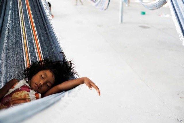 An indigenous Warao child from the Orinoco Delta in eastern Venezuela, sleeps on a hammock at a shelter in Pacaraima, Roraima state, Brazil November 15, 2017. Picture taken November 15, 2017. REUTERS/Nacho Doce