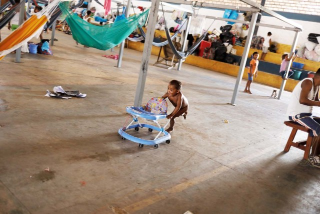 An indigenous Warao child from the Orinoco Delta in eastern Venezuela, plays in front of hammocks hanging from metal structures provided by the United Nations refugee agency UNHCR at a shelter in Boa Vista, Roraima state, Brazil November 18, 2017. Picture taken November 18, 2017. REUTERS/Nacho Doce