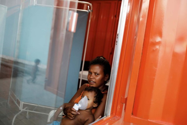 An indigenous Warao child from the Orinoco Delta in eastern Venezuela, receives nebulizer therapy by his mother at a shelter in Pacaraima, Roraima state, Brazil November 15, 2017. Picture taken November 15, 2017. REUTERS/Nacho Doce