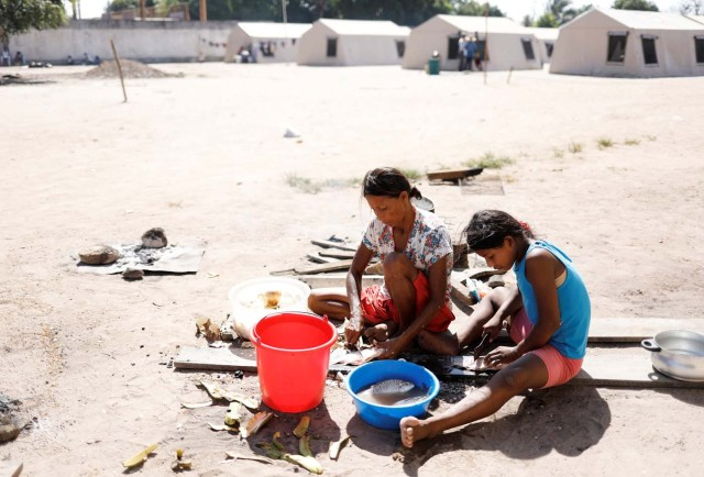 Indigenous Warao women from the Orinoco Delta in eastern Venezuela, cut fishes in front of tents at a shelter in Boa Vista, Roraima state, Brazil November 18, 2017. Picture taken November 18, 2017. REUTERS/Nacho Doce
