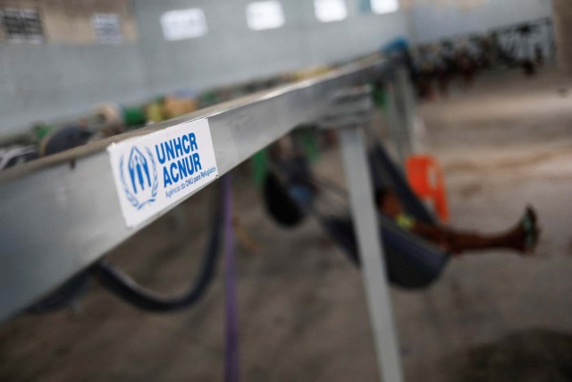 The logo of United Nations refugee agency UNHCR is seen on metal structures they provided and where hammocks hang for members of the indigenous Warao people from the Orinoco Delta in eastern Venezuela, at a shelter in Pacaraima, Roraima state, Brazil November 15, 2017. Picture taken November 15, 2017. REUTERS/Nacho Doce