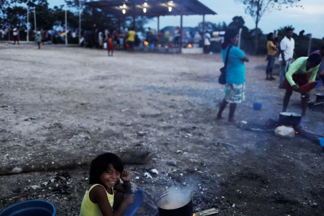 An indigenous Warao child from the Orinoco Delta in eastern Venezuela, smiles next to food at a shelter in Pacaraima, Roraima state, Brazil November 15, 2017. Picture taken November 15, 2017. REUTERS/Nacho Doce