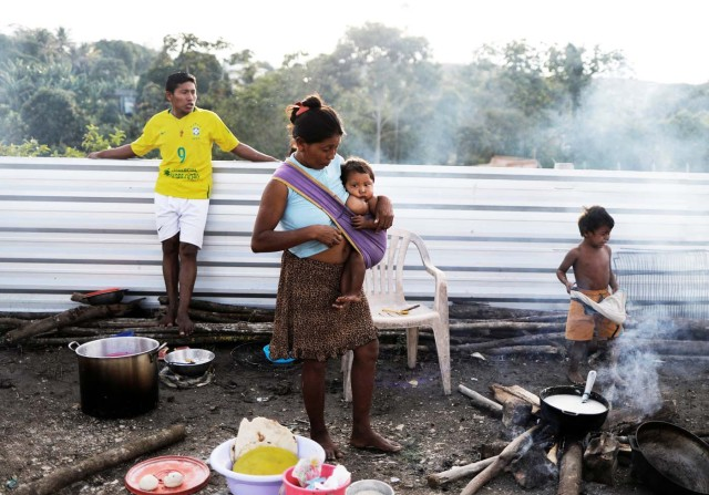 Indigenous Warao people from the Orinoco Delta in eastern Venezuela, stand next to food at a shelter in Pacaraima, Roraima state, Brazil November 15, 2017. Picture taken November 15, 2017. REUTERS/Nacho Doce TEMPLATE OUT