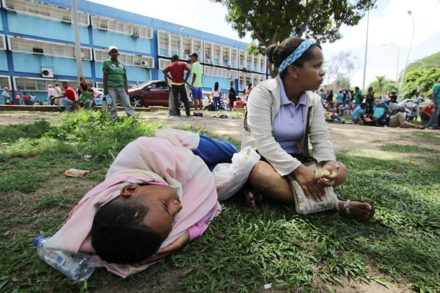 People lay on the grass outside a health center as they wait to get treatment for malaria, in San Felix, Venezuela November 3, 2017. Picture taken November 3, 2017. REUTERS/William Urdaneta