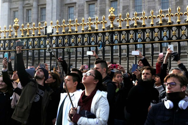 Tourists take pictures outside Buckingham Palace after Prince Harry announces his engagement to Meghan Markle, in London, Britain, November 27, 2017. REUTERS/Darrin Zammit Lupi