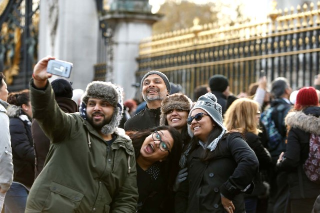 Tourists take pictures outside Buckingham Palace after Prince Harry announced his engagement to Meghan Markle, in London, Britain, November 27, 2017. REUTERS/Darrin Zammit Lupi