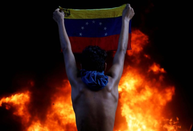 "A protester holds a national flag as a bank branch, housed in the magistracy of the Supreme Court of Justice, burns during a rally against Venezuela's President Nicolas Maduro, in Caracas, Venezuela June 12, 2017. REUTERS/Carlos Garcia Rawlins/File Photo      SEARCH ""POY GLOBAL"" FOR THIS STORY. SEARCH ""REUTERS POY"" FOR ALL BEST OF 2017 PACKAGES.    TPX IMAGES OF THE DAY"
