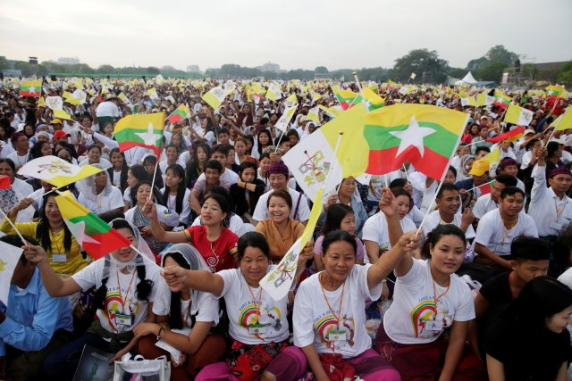 Catholic faithful wave Myanmar and Vatican City flags as they attend a mass led by Pope Francis at Kyite Ka San Football Stadium in Yangon, Myanmar November 29, 2017. REUTERS/Max Rossi