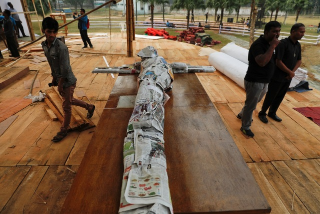 A wooden crucifix is wrapped in newspapers as it's brought to where Pope Francis will hold a mass in a park in Dhaka, Bangladesh November 29, 2017. REUTERS/Damir Sagolj