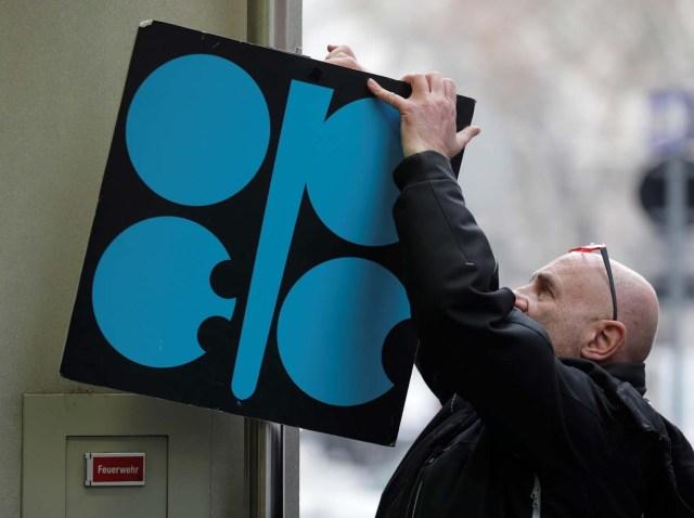 Un hombre acomoda un cartel con el logotipo de la OPEP en la entrada de la sede de la organización antes de una reunión de ministros de petróleo, en Viena. 29 de noviembre de 2017. REUTERS/Heinz-Peter Bader